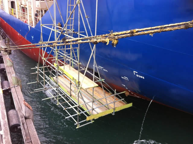 Suspended scaffolding beside ship